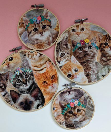 Handgemaakte borduurwerken van katten met bloemenkrans